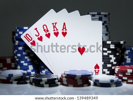 Royal Flush of Hearts balanced between poker chips on white. Gambling concept