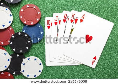Royal flush. Playing cards isolated on a green background with poker chips scattered  - stock photo