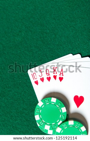 Royal Flush poker card sequence near chips on a green table. Risky entertainment of gambling - stock photo