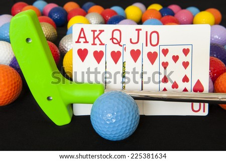 Royal flush poker hand with mini golf putter and balls - stock photo