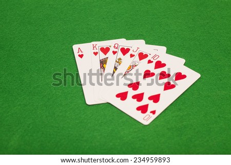 Royal flush poker playing cards on green felt background