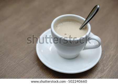 Royal milk tea inside white cup on the wooden table