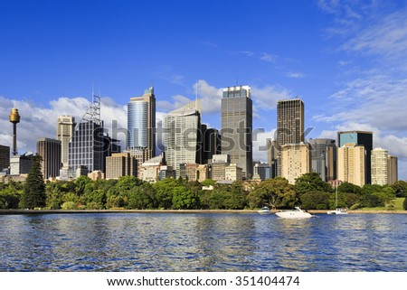 Royal national park in SYdney with City high rise business towers rising above green trees and harbour cove on a sunny day - stock photo