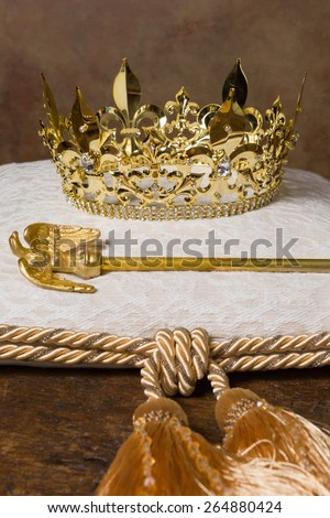 Royal scepter and golden crown on a cream cushion - stock photo