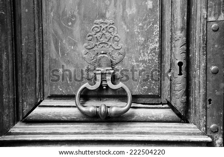 Royal style doorknocker on old wooden door. Paris, France. Aged photo. Black and white. - stock photo