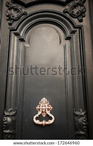 Royal style golden doorknocker on black wooden door.  - stock photo