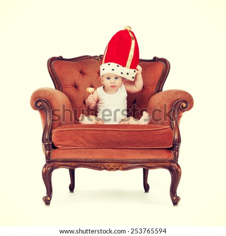 royalty and happy child concept - adorable royal baby boy in king hat with lollipop - stock photo