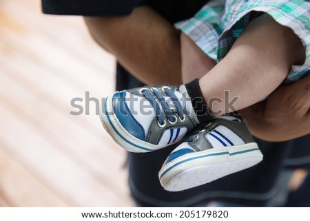 Royalty free image of a baby boy's legs, wearing sneakers, being held by father. Shallow depth of field. - stock photo