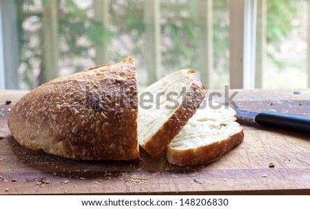 Royalty free stock image of a fresh loaf of crusty bread on a cutting board