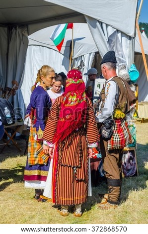 ROZHEN, BULGARIA, JULY 18, 2015: Women dressed in traditional bulgarian dresses are selling souvenirs during rozhen folklore festival near chepelare. - stock photo