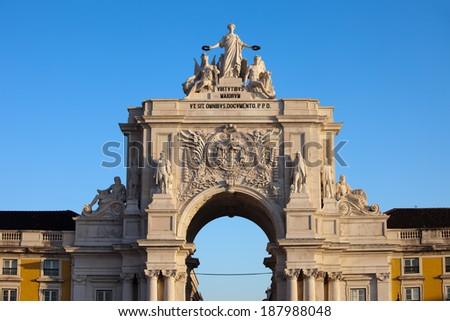 Rua Augusta Arch at sunrise in Lisbon, Portugal. Statues at the top: Allegory of Glory rewarding Valor and Genius, coat of arms of Portugal below. - stock photo