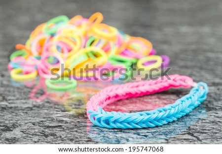 Rubber band bracelet on reflective background - stock photo