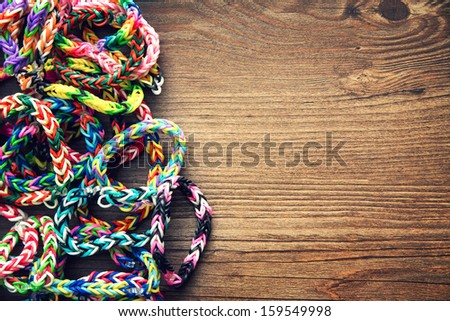 Rubber band loom bracelets on a wooden table background, vintage processed - stock photo