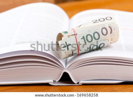 Rubber band on money, rolled bunch of hundred polish zloty banknotes, one and two hundred paper money lying on open book, objects on table in horizontal orientation, nobody. - stock photo