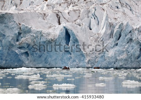 rubber boat in front of a glacier in Svalbard, Arctic. - stock photo