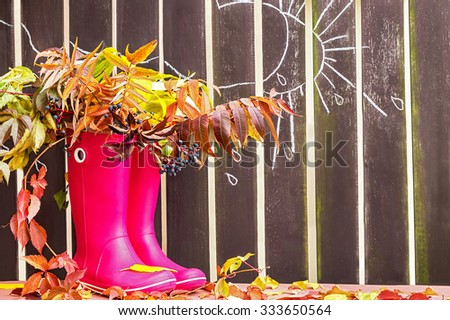 Rubber boots (rainboots) and autumnal leaves are on the wooden fence background with drawing rain drops, cloud and sun. Autumn. Copy space for your text. Creative, activity, leisure, travel concept.  - stock photo