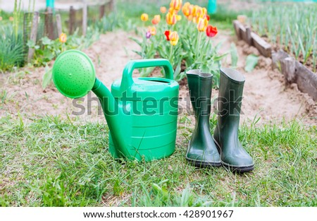 Rubber boots with watering can on grass - spring and summer concept
