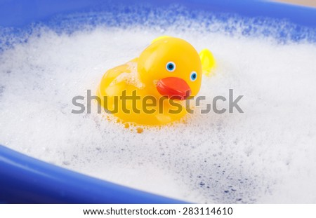 Rubber duck covered in soap - stock photo