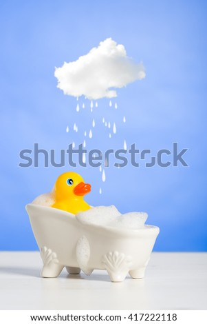 Rubber duck taking a bath with cloud over head - stock photo