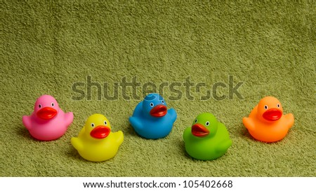 Rubber ducks isolated on a green towel, with room for text - stock photo