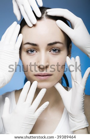 rubber gloves touching womans face - stock photo