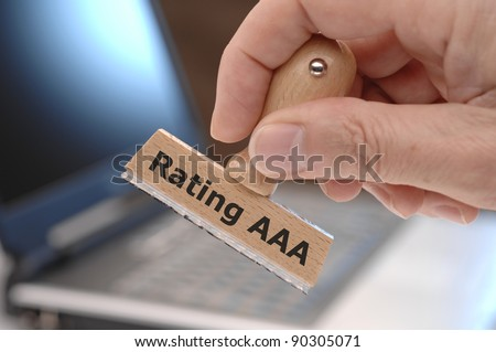 rubber stamp in hand with financial market ranking AAA - stock photo