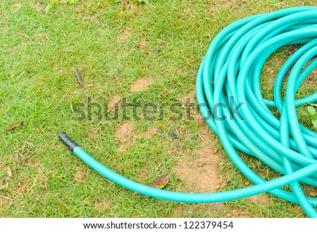 Rubber tube for watering plants in the garden - stock photo