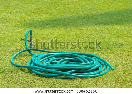 Rubber tube on grass in the garden - stock photo