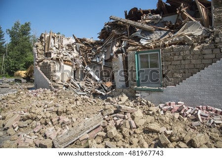 Rubble in front of an old mud brick building in the process of being torn down.