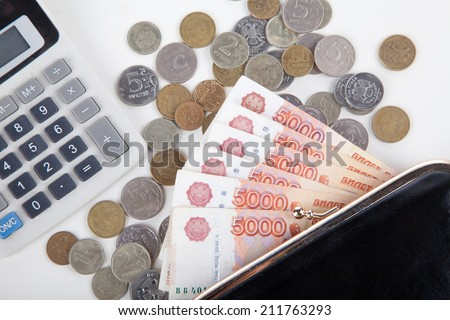 Ruble money in black purse and calculator on white background