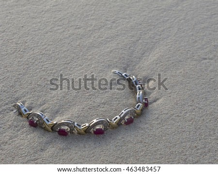 ruby bracelet being swallowed by the sand