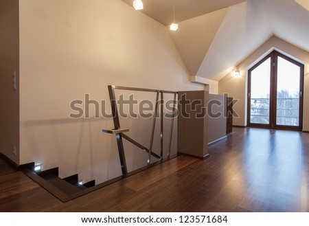 Ruby house - Contemporary attic with staircase and huge balcony door - stock photo