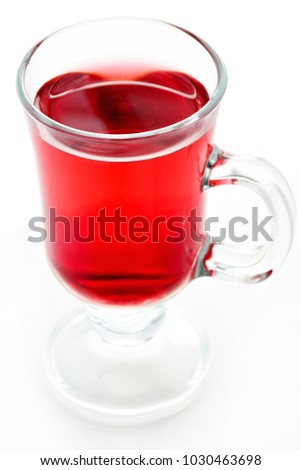 Ruby red herbal pomegranate tea in glass mug.  Vertical format and shot in natural light
