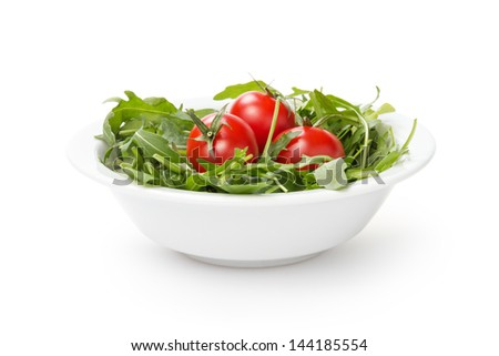 ruccola and tomatoes in white bowl, isolated on white