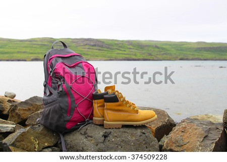 Rucksack and yellow boots on the mountain background - stock photo