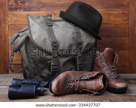 Rucksack with old boots, binocular and hat on wooden background. Traveller concept