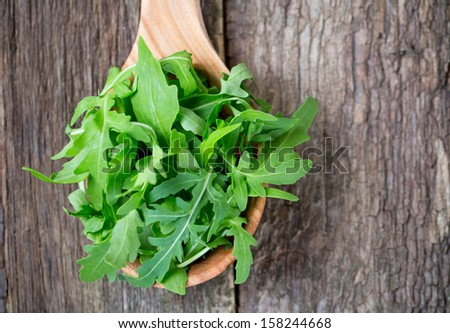 rucola in a wooden spoon on a wooden table - stock photo