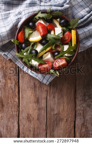 rucola salad with cheese, olives and tomatoes, vertical view from above  - stock photo