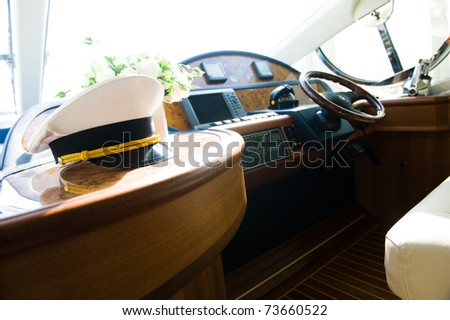 Rudder, compass and captain's hat on yacht - stock photo