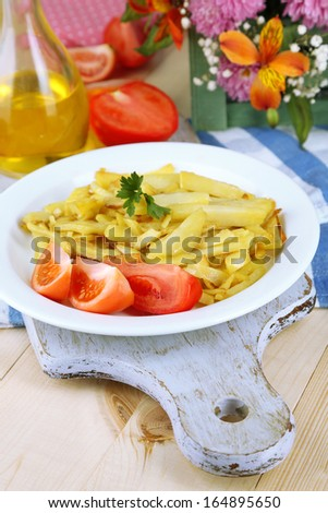 Ruddy fried potatoes on plate on wooden table close-up