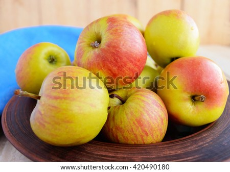 Ruddy ripe green apples in a brown bowl on a light wooden background. Close up