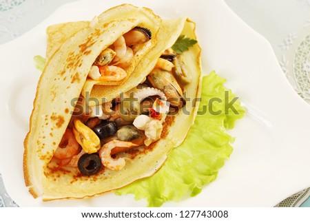 Ruddy thin pancake stuffed with seafood salad - stock photo