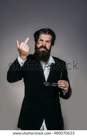 Rude man bearded hipster male in suit with vintage glasses gives middle finger on grey wall