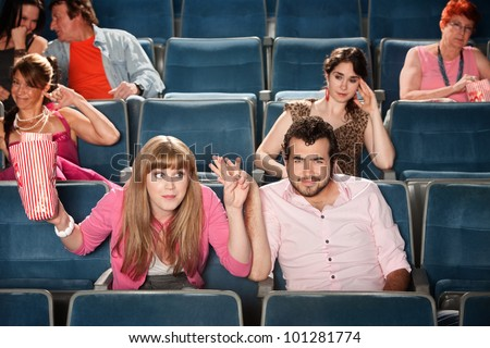 Rude young woman with man in theater audience - stock photo