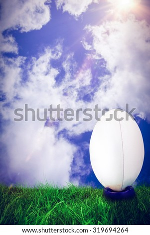 rugby ball against bright blue sky with clouds