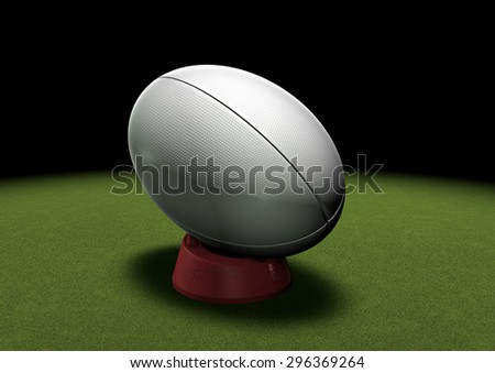 Rugby ball on a kicking tee waiting to be kicked. Spotlight on grass.