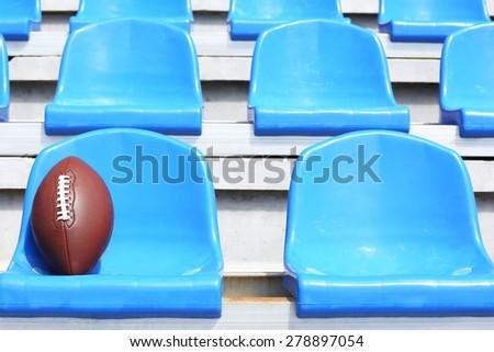 Rugby ball on stadium seat - stock photo