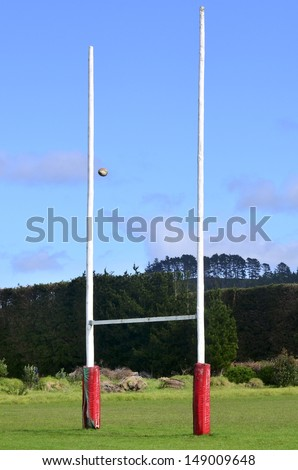 Rugby ball passing through Goal posts for football, rugby union or league on field. - stock photo