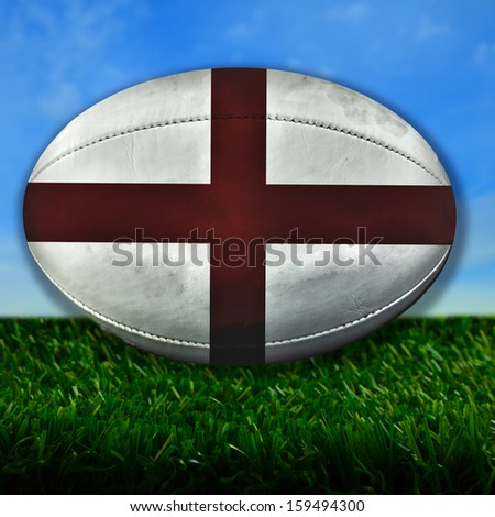 Rugby ball with England flag over grass - stock photo