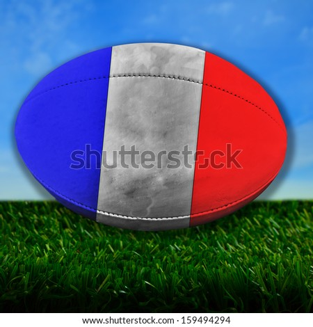 Rugby ball with France flag over grass - stock photo